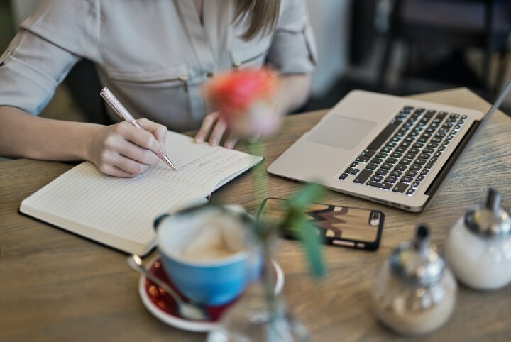 a female student sits at a table, she's writing in a notebook in front of her open laptop. A coffee cup and other desk decorations are just out-of-focus in the foreground